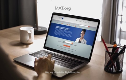 A still from the a TV ad featuring the MAT.org website, showing a person using a laptop to access the homepage of the site.