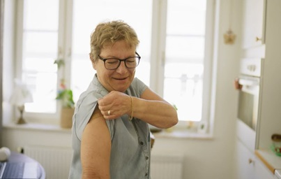 A photograph showing a smiling older person raising their sleeve to show a small bandage on their shoulder, proudly showing a recent vaccination
